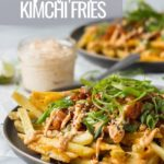 plate of french fries with kimchi, cheese, and green onions