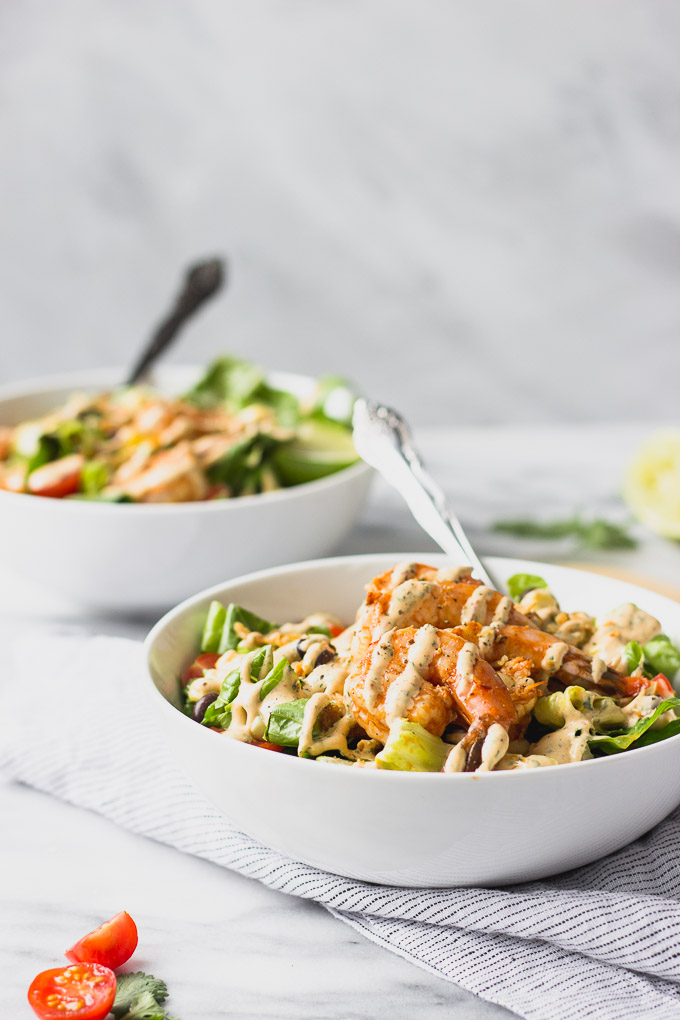 side view of two bowls of spicy chipotle shrimp salad with fork inside