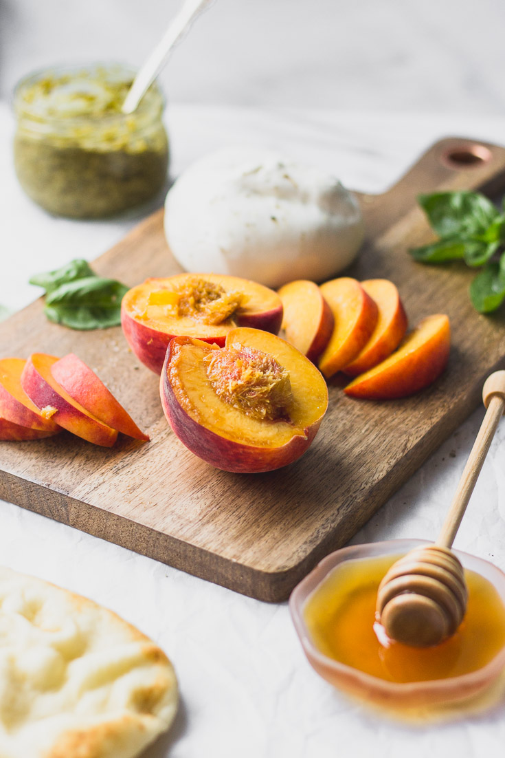 Peaches sliced on cutting board next to burrata, honey and pesto.