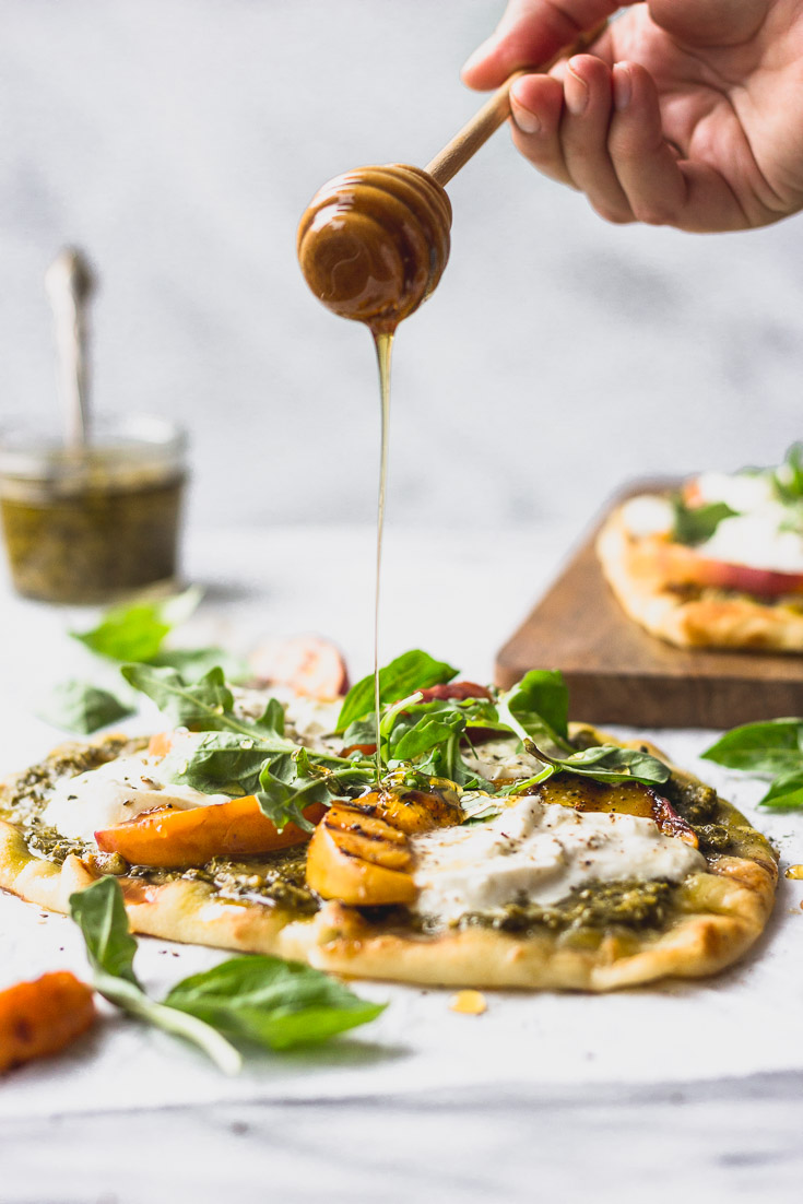 Honey drizzling on flatbread with peach slice.