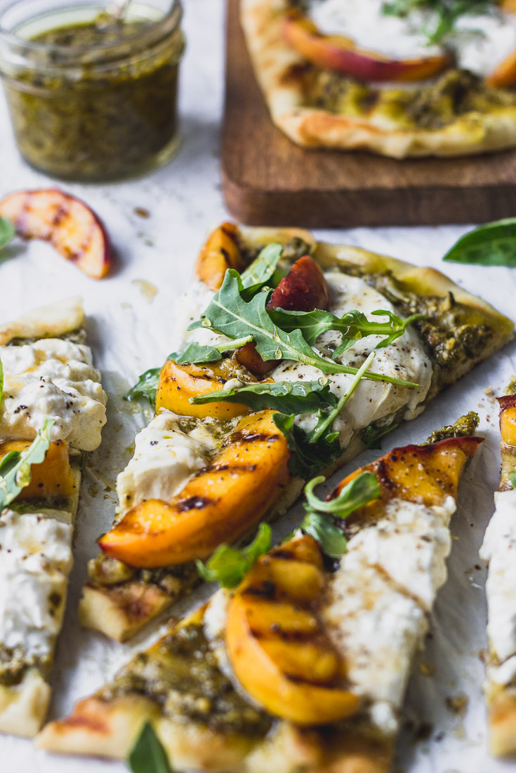 Side view of slice of flatbread with burrata, grilled peach, and arugula.