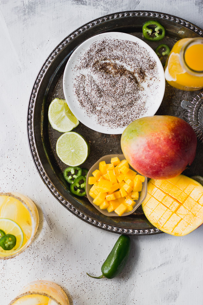 spicy mango margarita ingredients on a serving tray with lime, mango, salt and chili mix, and jalapeno