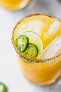 up close low ball glass with chili salt rim with jalapeno and lime
