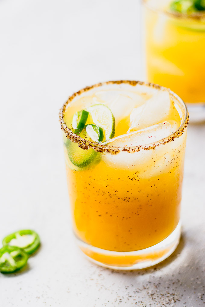 low ball glass with spicy mango margarita with chili pepper rim and jalapeno