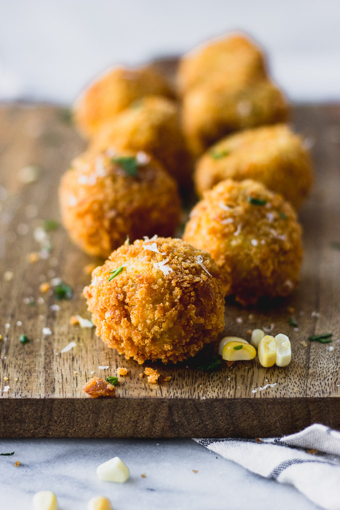 scalloped corn arancini on serving platter in a line