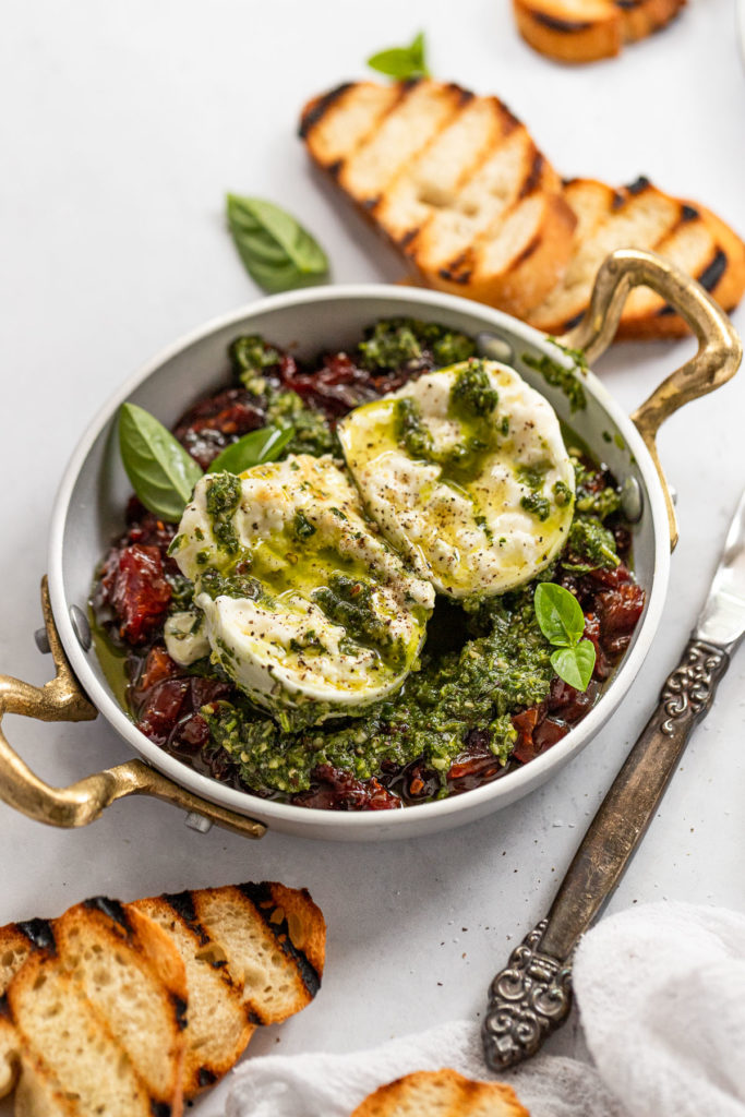 Side view of burrata on top of pesto and tomato jam with baguette slices.