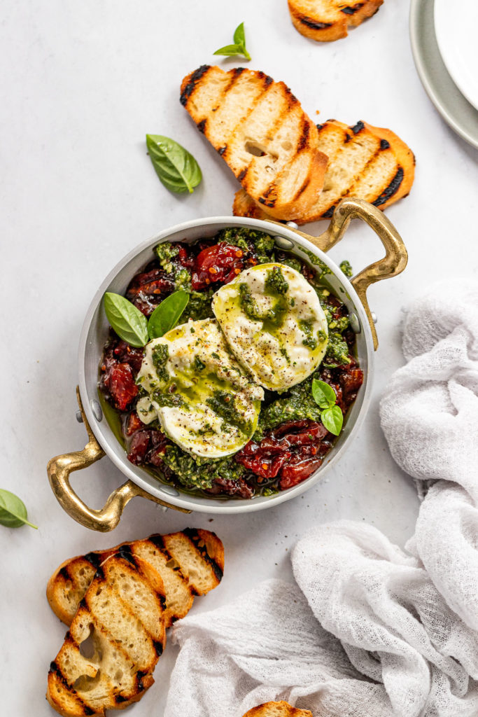 Serving dish with tomato jam, pesto, and burrata next to baguette slices.