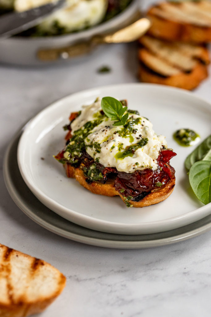 Crostini with burrata appetizer spread on top and basil garnish.