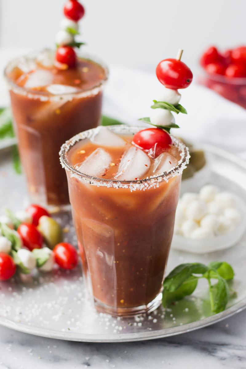 two glasses of bloody mary with mozzarella, tomato, and basil on a tray