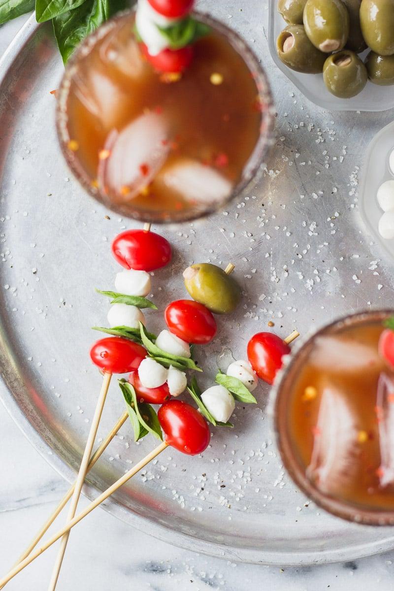 mozzarella, tomatoes, basil skewers next to bloody marys