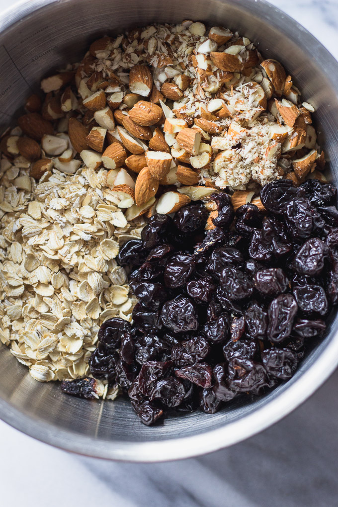 oats, almonds, and dried cherries ingredients in a silver bowl for cherry almond granola bars