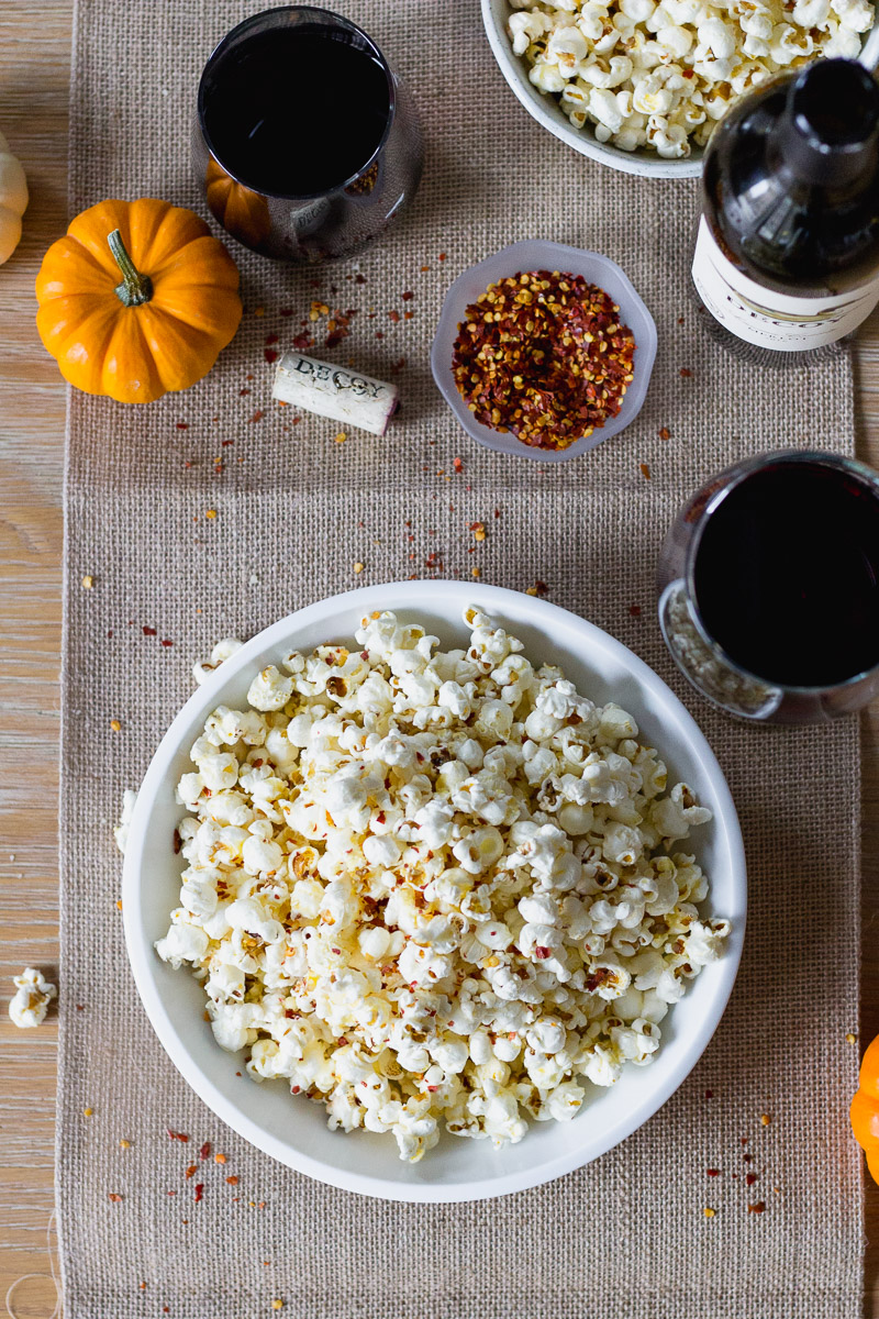 bowl of popcorn next to wine bottle and wine