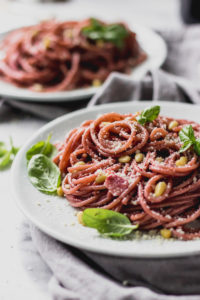 Red wine spaghetti with basil garnish on a plate.