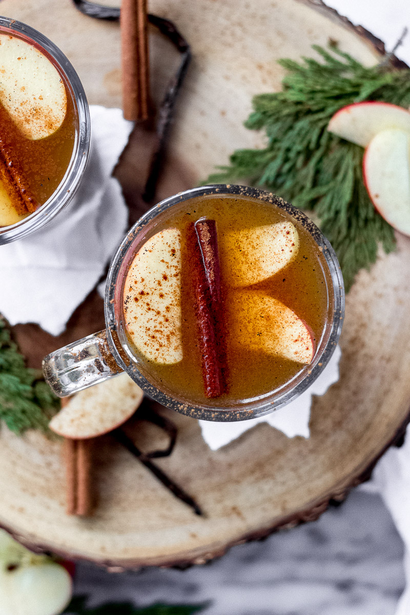 apple cider vanilla bean cocktail on wood tray by fork in the kitchen