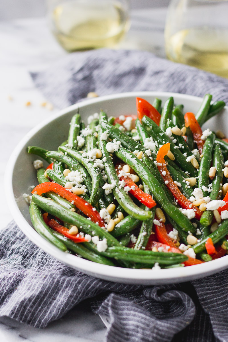 green beans with red bell pepper, pine nuts, and goat cheese in white bowl by fork in the kitchen