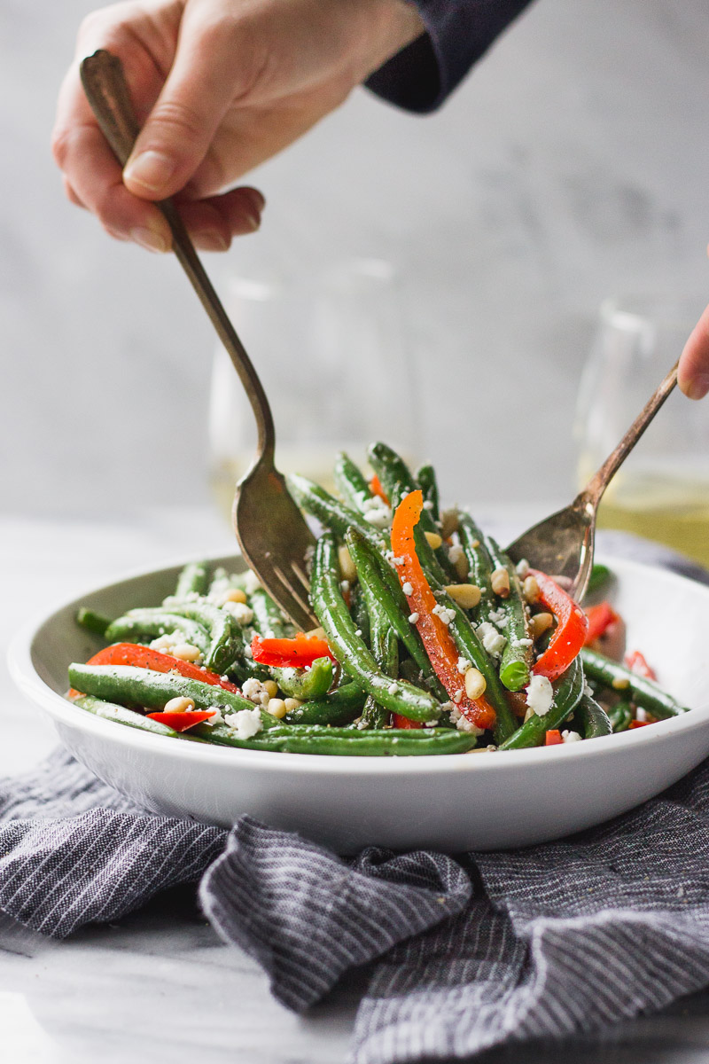 green beans with red bell pepper, pine nuts, and goat cheese in white bowl with hands grabbing by fork in the kitchen