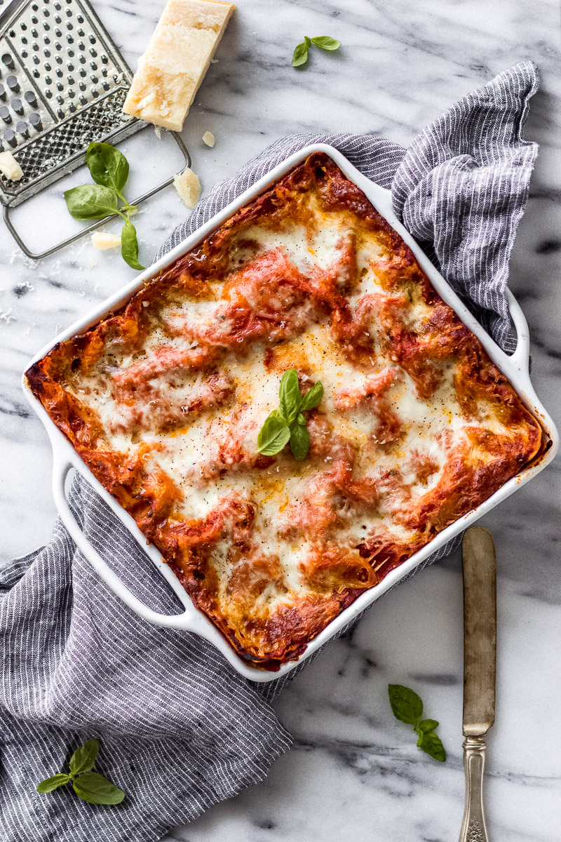 Baked lasagna in pan with linen next to parmesan and basil.