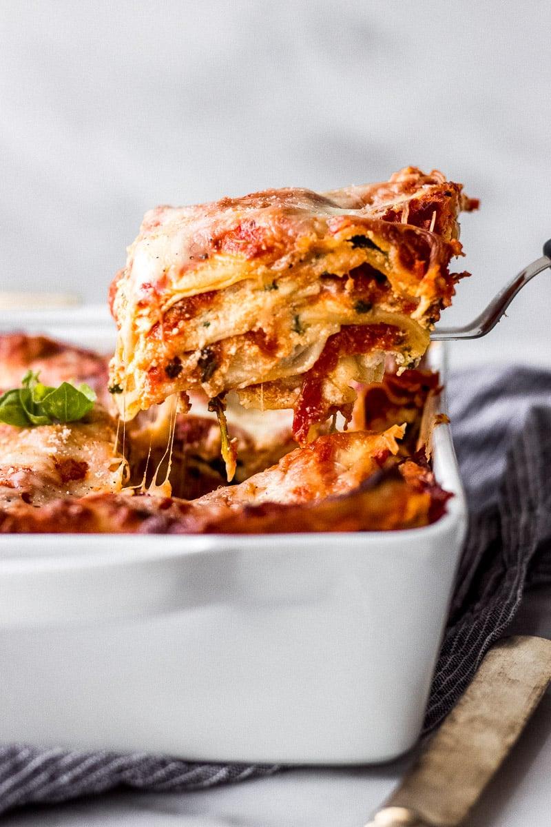 Spatula lifting slice of lasagna out of baking dish.
