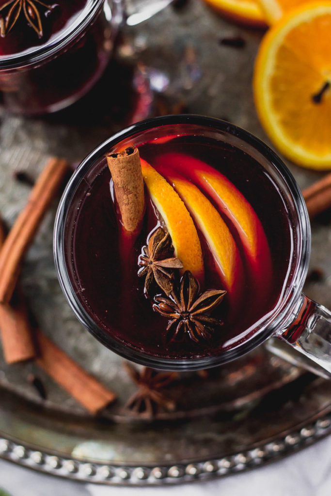 overhead look into glass mug with mulled red wine, cinnamon, and orange slices on tray by fork in the kitchen