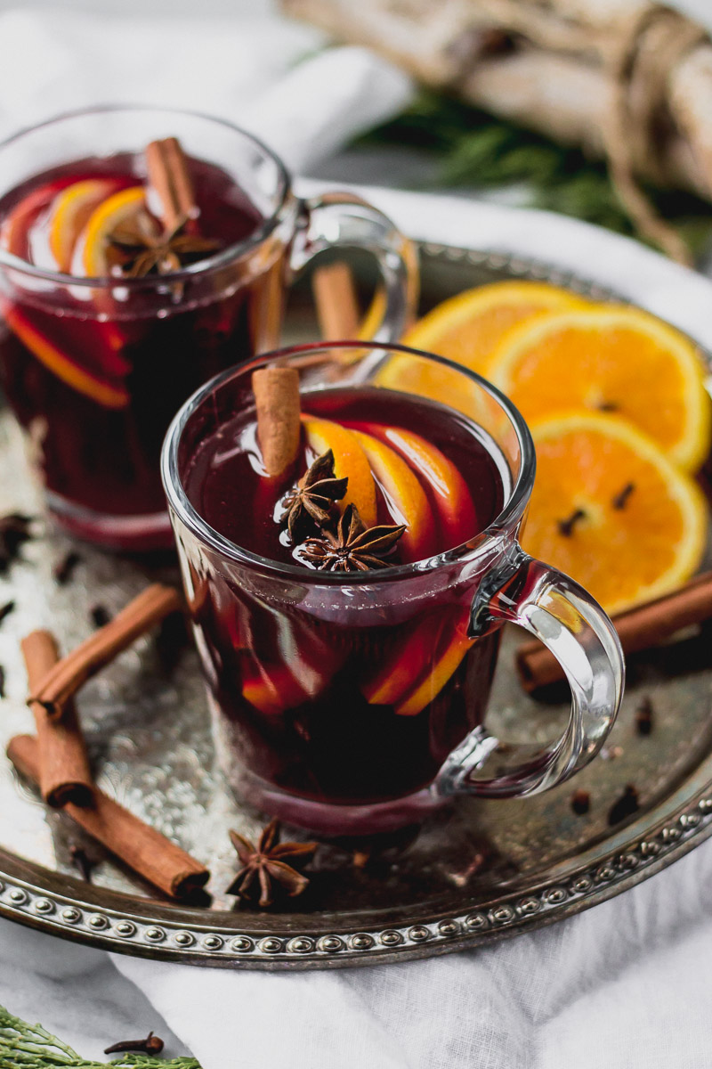 glass mug with mulled red wine, cinnamon, and orange slices on tray
