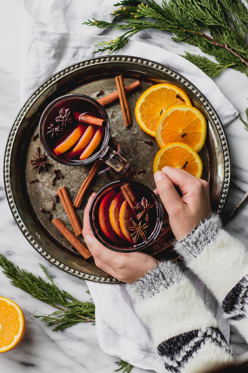 hands holding mulled red wine