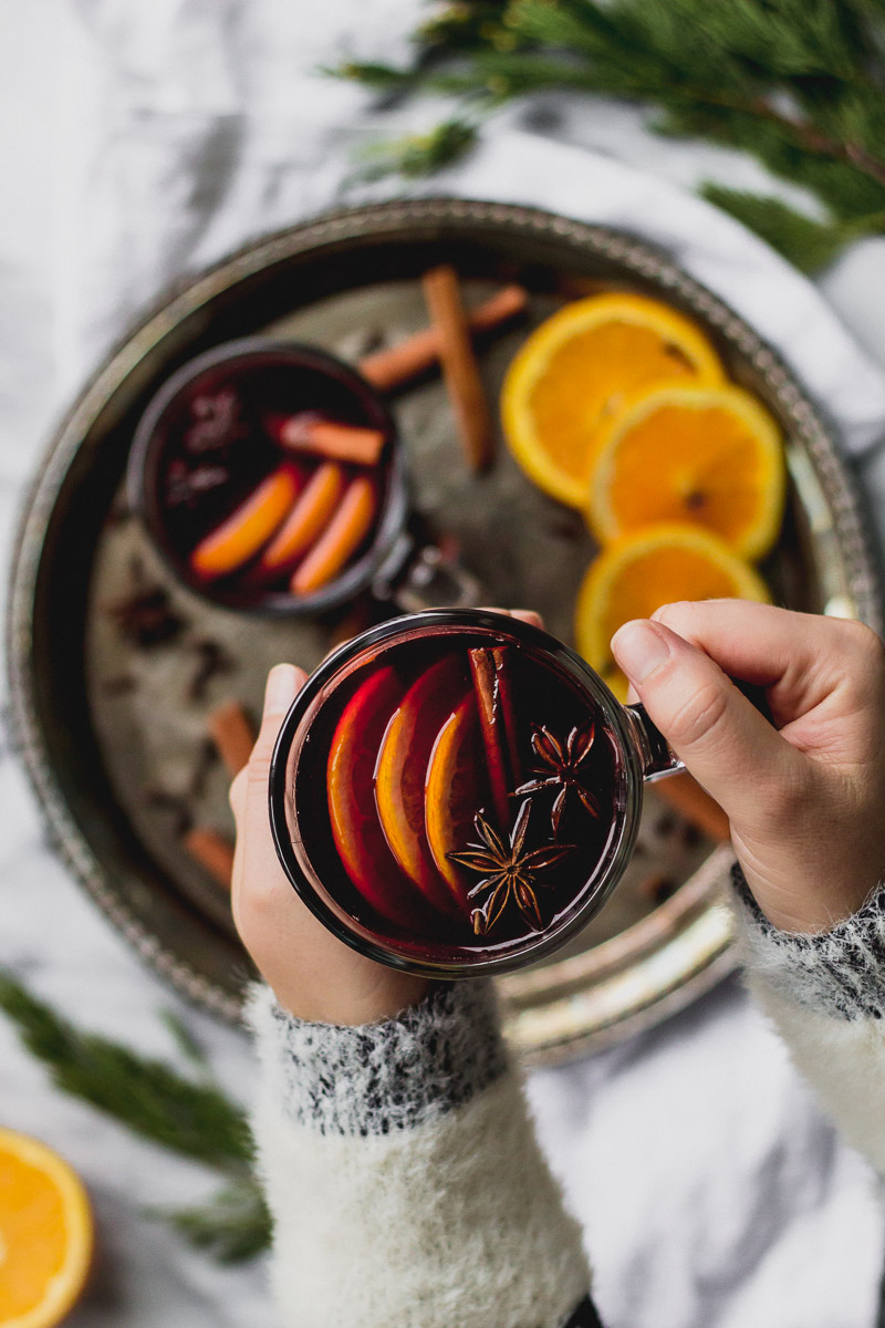 hands holding glass mug with mulled red wine