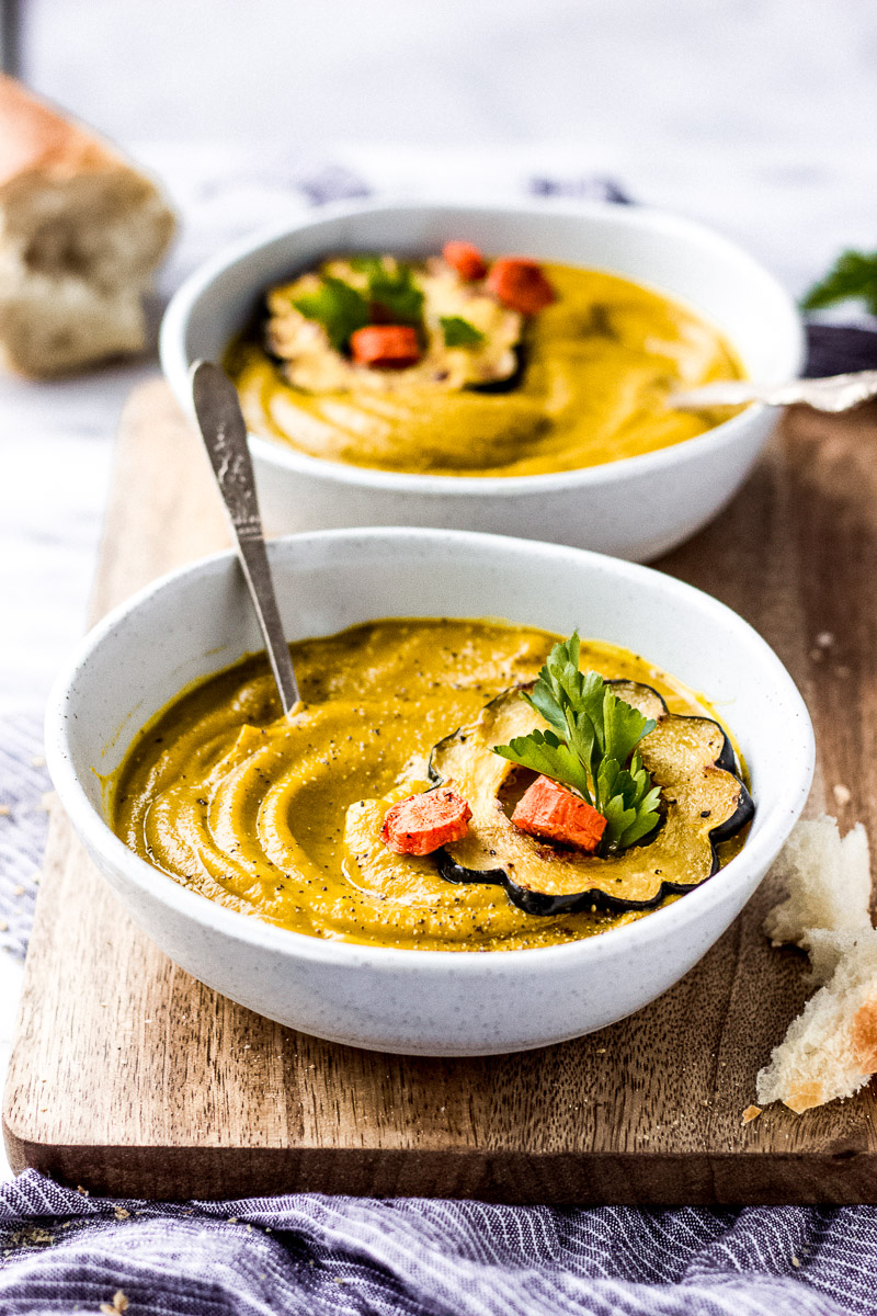 Curried Carrot Squash Soup in a white bowl with spoon by Fork in the Kitchen