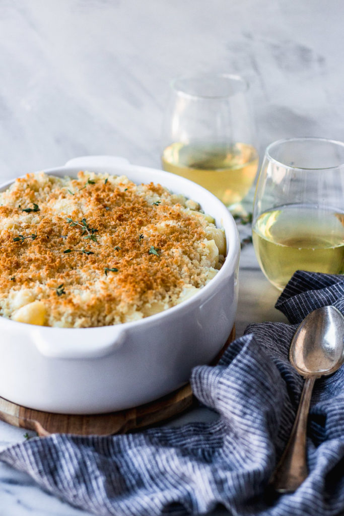 Baked mac and cheese in dish next to spoon.
