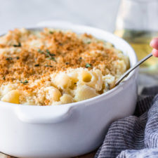 white wine mac and cheese being scooped out of casserole dish by fork in the kitchen