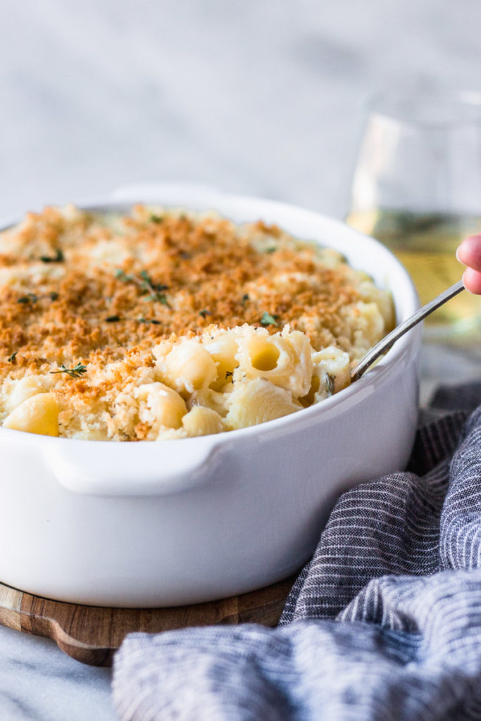 Hand scooping out macaroni from dish.