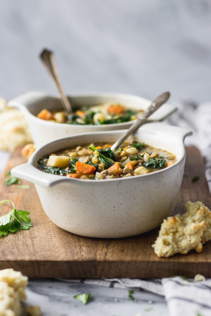 healthy lentil soup in cream bowl with spoon and biscuit side by fork in the kitchen