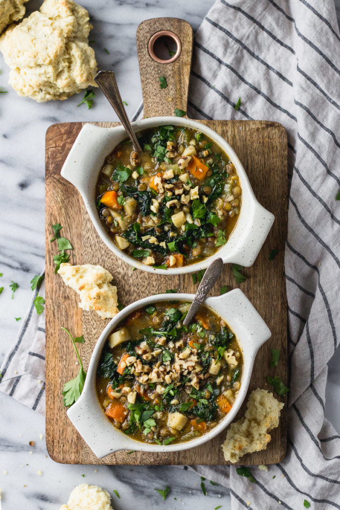 healthy lentil soup in cream bowl with biscuit side by fork in the kitchen