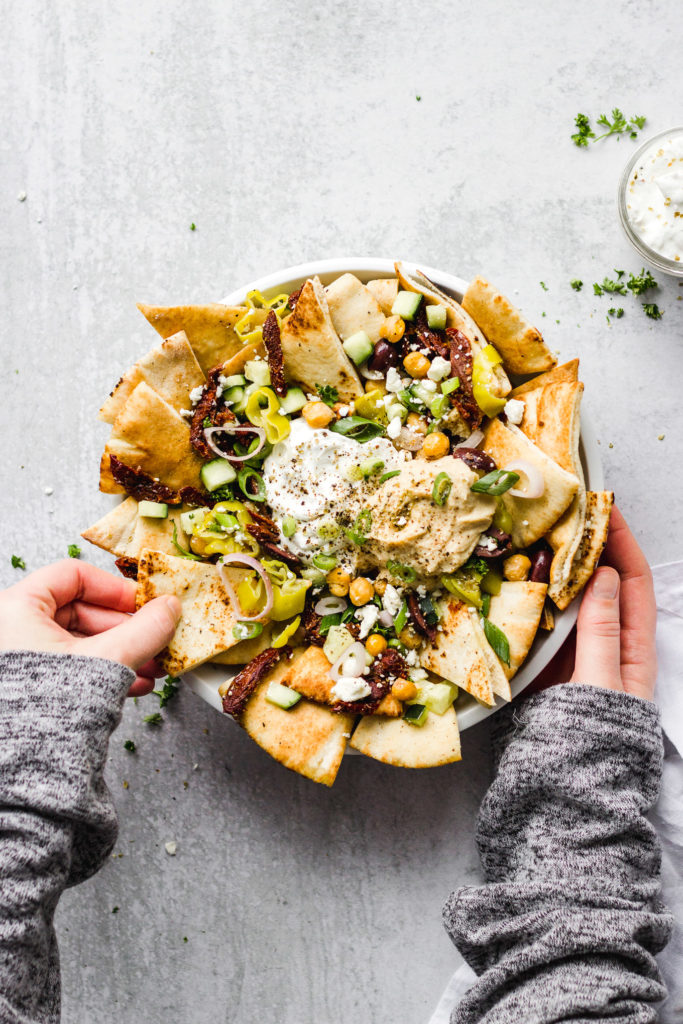 bowl of greek nachos with dip by fork in the kitchen