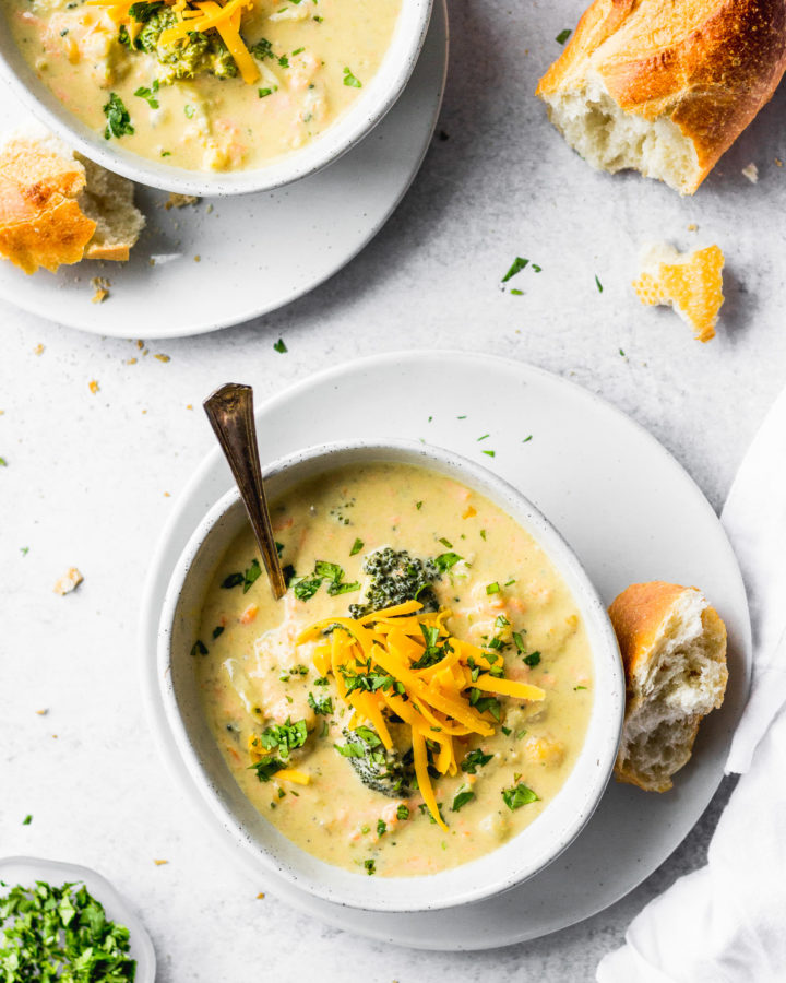 broccoli cauliflower cheddar soup in bowls with baguette by fork in the kitchen