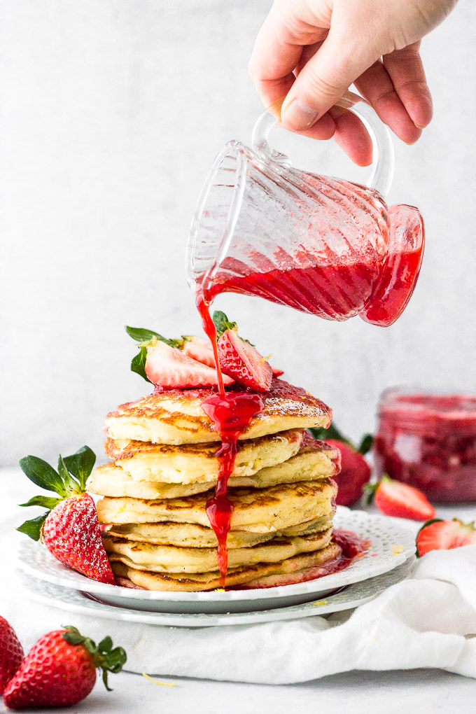 lemon mascarpone pancakes with strawberry sauce pouring, stacked on plate by fork in the kitchen