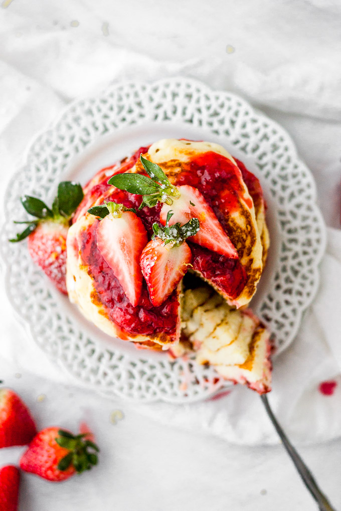 lemon mascarpone pancakes with strawberry sauce stacked on plate by fork in the kitchen
