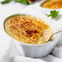 Creme brulee in white ramekin with spoon.
