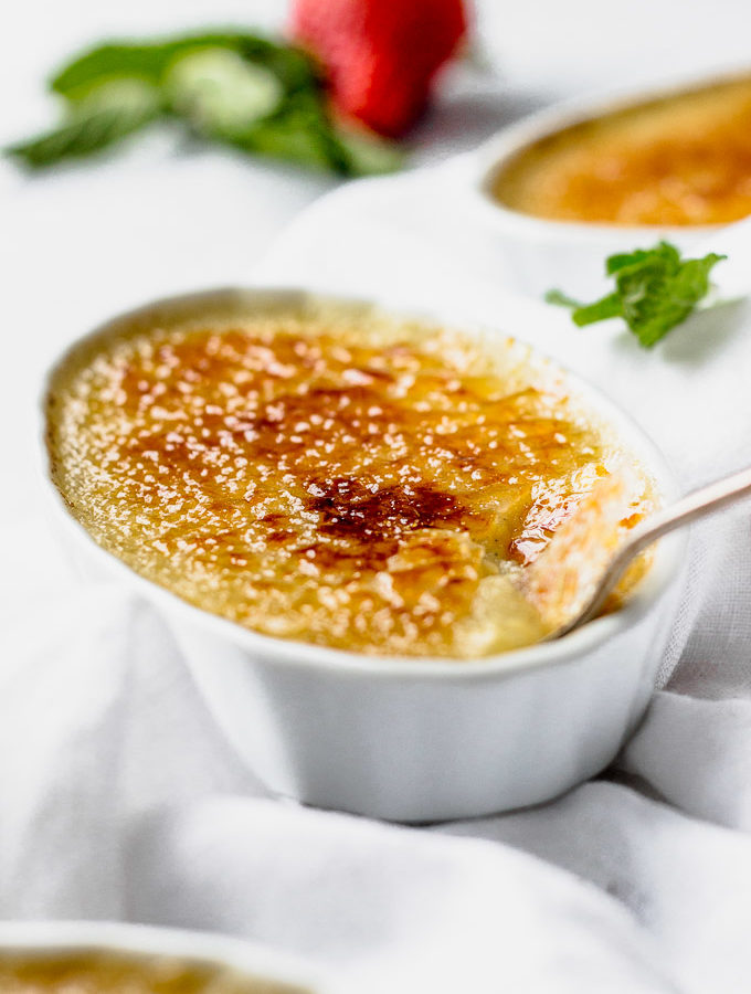 vanilla bean creme brulee in white ramekin with berries and spoon by fork in the kitchen