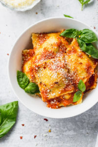 Bowl of cheese ravioli with basil leaves inside and around.