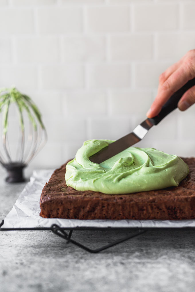 spreading mint cream cheese frosting on brownies