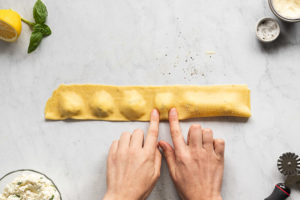 Pressing dough around cheese filling to form ravioli.