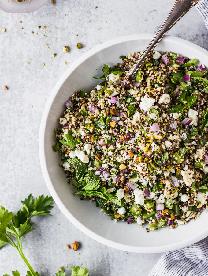 quinoa salad in white bowl with spoon by fork in the kitchen