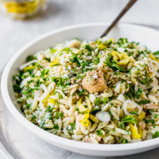 tuna orzo pasta salad in white bowl with spoon by fork in the kitchen
