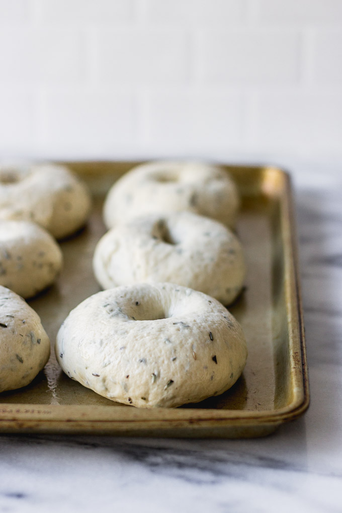 homemade rosemary bagels resting on pan