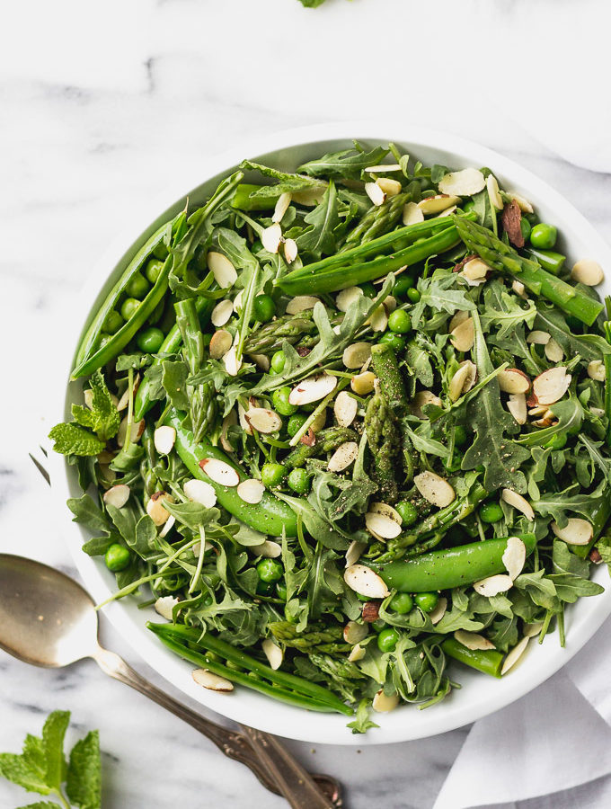 green vegetable salad with asparagus and peas in white bowl