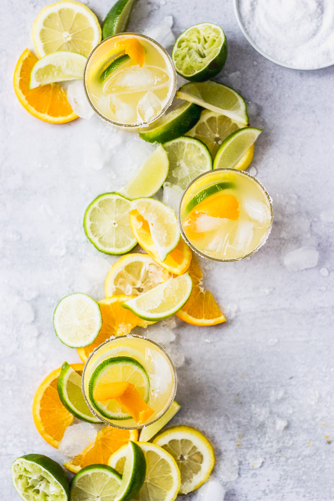 overhead citrus margaritas with orange and lime garnish
