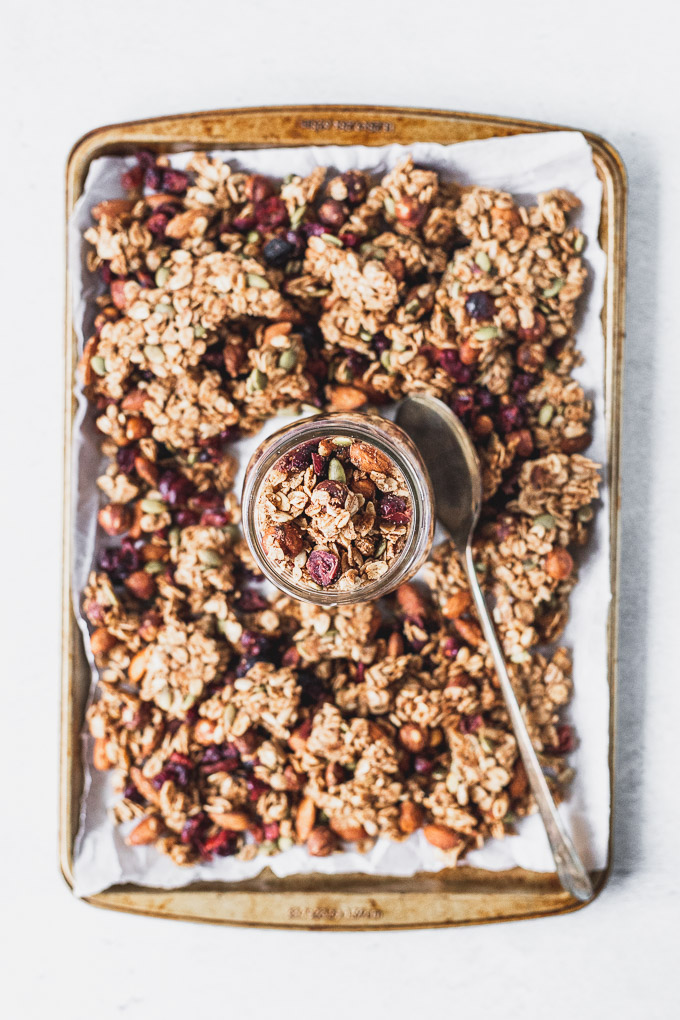 baking sheet with homemade cinnamon granola and a jar next to a spoon