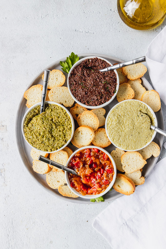 plate of mediterranean spreads with spoons and bruschetta toasts