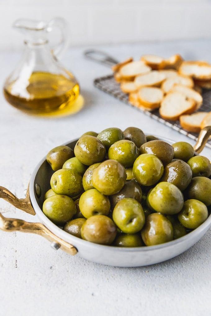 Bowl of Castelvetrano olives next to olive oil and baguette crisps.