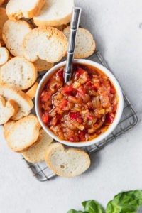 tomato onion spread in bowl next to crostini